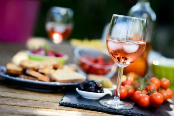 vacances été brunch la table de fête en plein air dans une arrière-cour de la maison avec apéritif, verre de rosé vin, une boisson fraîche et légumes biologiques - Photo