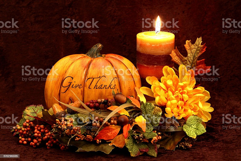 Thanksgiving still life with autumn colored candle, flower, pumpkin,...