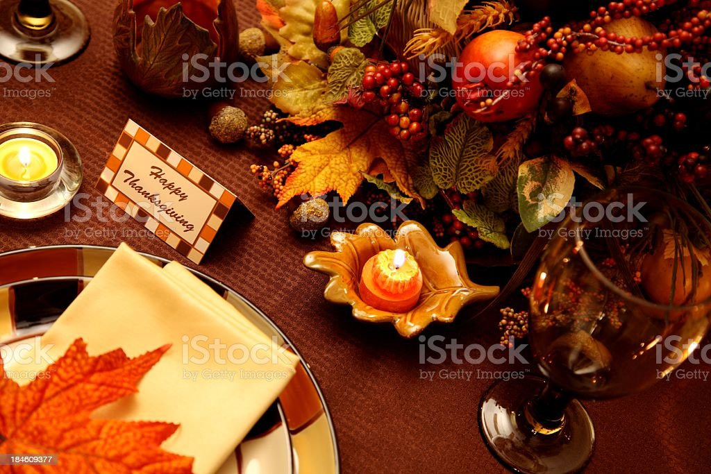 Thanksgiving Holiday table with a pumpkin candle, and leaves. Note...