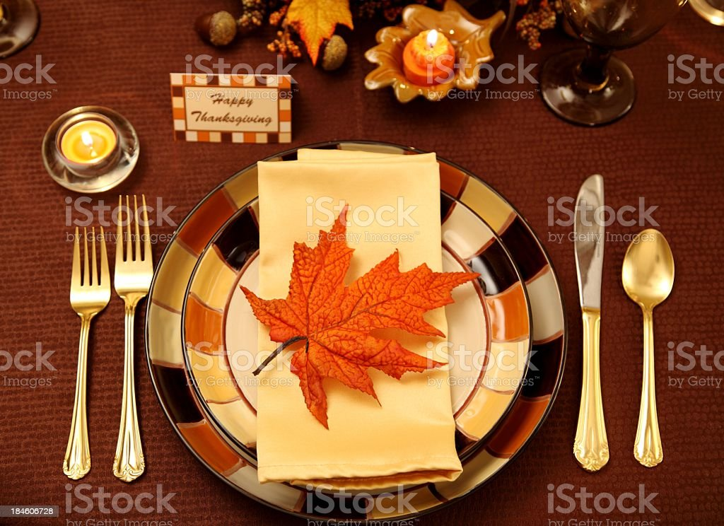 Thanksgiving Holiday table with autumn colored plates, candles, and...