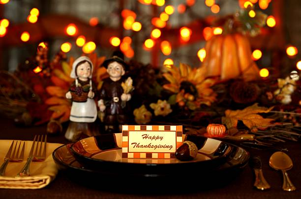 Holiday: Thanksgiving Table setting with pilgrims and lights Thanksgiving Holiday table setting with a pilgrim couple, pumpkins, sunflowers, lights and a note card saying Happy Thanksgiving on plate. Selective focus on text of the note card. Pilgrim couple is non copyrighted (see release), and the note card border is my design. pilgrim stock pictures, royalty-free photos & images