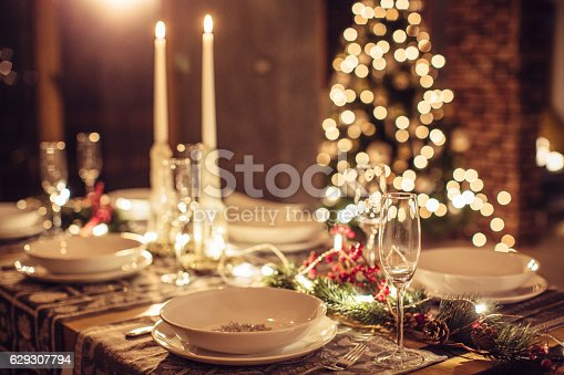 Table set up for Christmas dinner. Evening or night. Christmas tree in background.