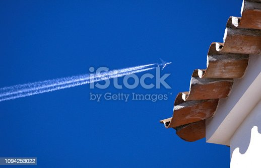 Jet aeroplane and condensation trail against a clear blue sky and a holiday villa, Spain