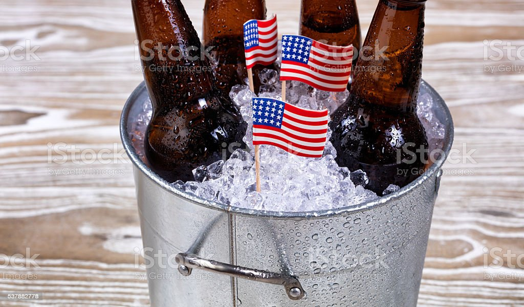 Holiday USA flags and bucket of ice cold beer stock photo