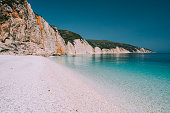 Holiday vacation scene. Fteri beach on Kefalonia Island, Greece. Most beautiful pebble beach with clear emerald blue sea water.