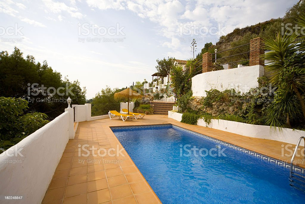 Holiday vacation villa swimming pool and sun bathing area royalty-free stock photo