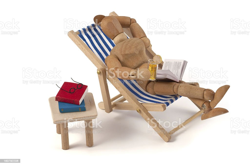 Holiday - wooden mannequin in deckchair with drink and books royalty-free stock photo