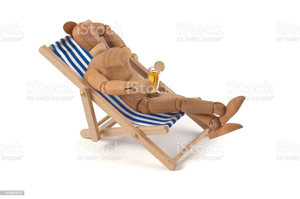 Holiday - wooden mannequin in deckchair with drink stock photo