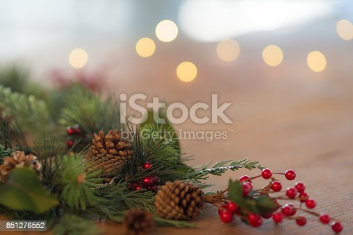 Close up shot of festive winter decorations. A Christmas wreath with red berries and pine cones lies on a rustic wood table. White Christmas lights twinkle in the background. Copy space is available in the upper right of the frame.