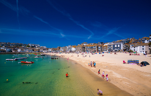 Holiday-makers play on a beach in Cornwall