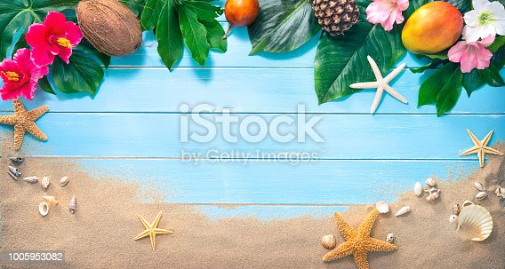 istock Holidays background with tropical flowers, leaves, exotic fruits and seashells on sand beach 1005953082
