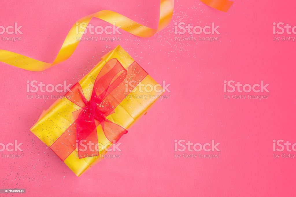 Holidays concept, flat lay composition. Yellow gift box with red bow...