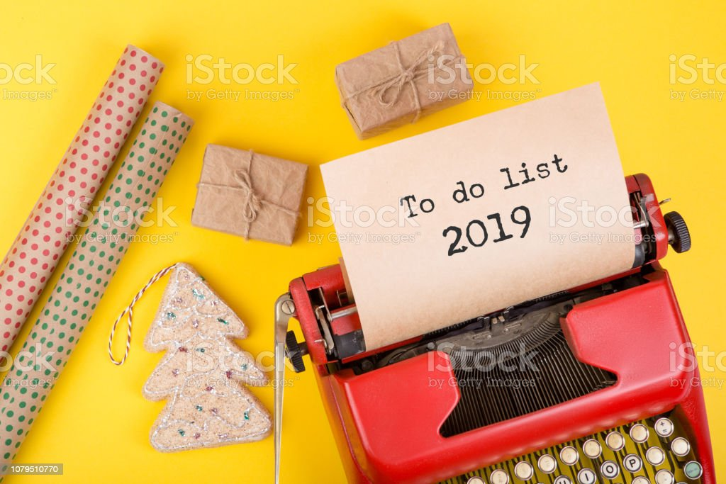 Holidays concept - red typewriter with text \'To do list 2019\', gift...