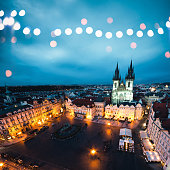 View on illuminated Old Town Square and Tyn Church from the Astronomical Clock Tower at night (Prague, Czech Republic). Defocused christmas lights in the foreground.