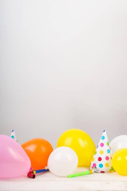 urlaub, party, feiern. entzückende muster für geburtstag oder jubiläum glückwunsch auf die weiße fläche der tabelle es gibt viele luftballons, partyhüte und pfeifen. freiraum für text - einladungskarten kostenlos stock-fotos und bilder
