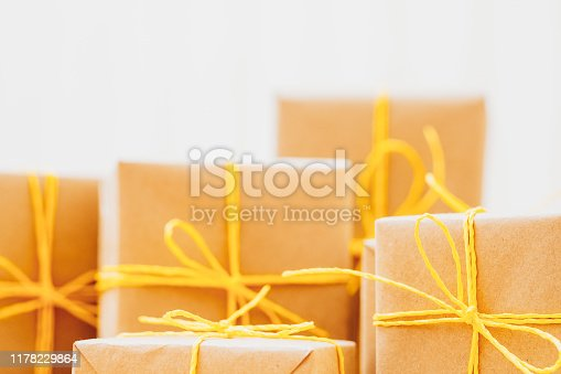 Holidays present collection. Closeup of beige paper gift boxes over white background. Copy space.