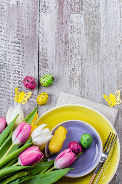 holidays spring background. easter table setting with spring tulips, colorful quail eggs and cutlery on shappy wooden background. copy space, top view - easter brunch stock photos and pictures