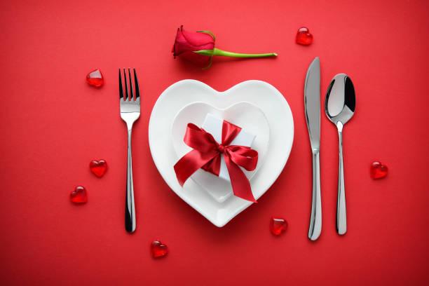 urlaub tischdekoration mit einer geschenkbox auf rotem grund - besondere geschenke stock-fotos und bilder