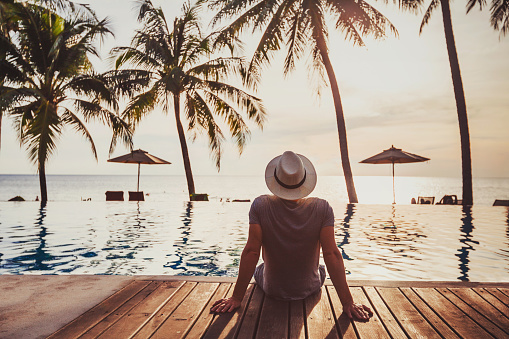 Holidays, tourist relaxing in luxury beach hotel near luxurious swimming pool.