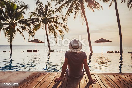 istock Holidays, tourist relaxing in luxury beach hotel near luxurious swimming pool. 1059344876