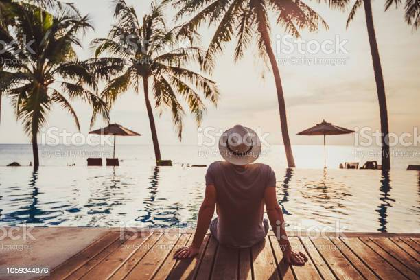 Photo of Holidays, tourist relaxing in luxury beach hotel near luxurious swimming pool.