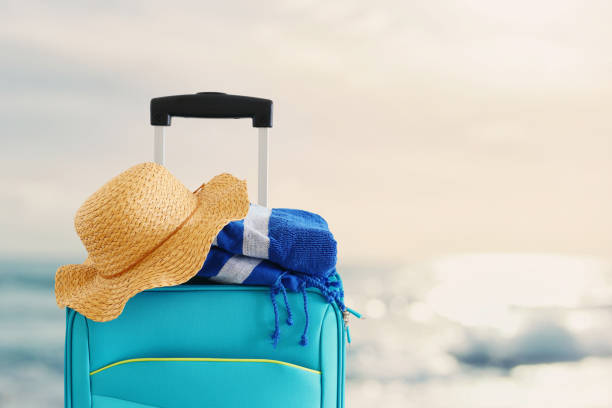 holidays. travel concept. blue suitcase with female hat and beach towel infront of tropical background – zdjęcie
