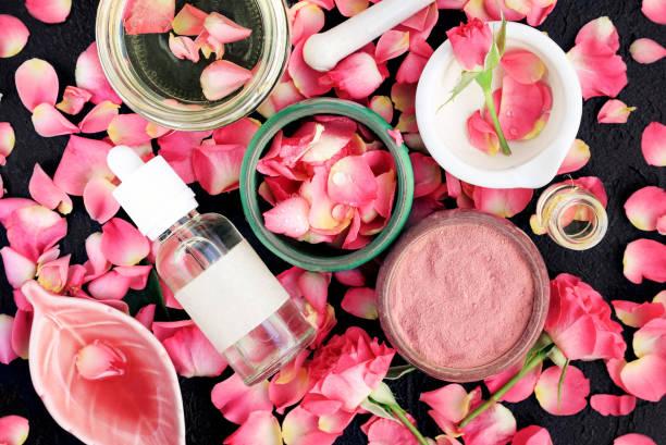 ganzheitliche kosmetische produkte in flaschen, gläser mit rosenblättern und rosa tonpulver - makeup selbst gemacht stock-fotos und bilder