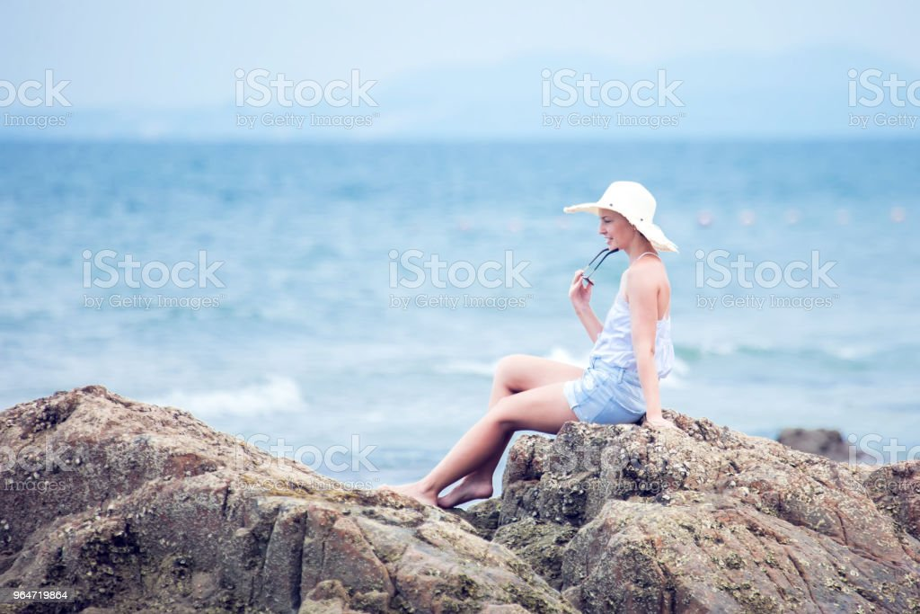 holliday,relax,nature.Beautiful young girl woman sits on the beach, dreaming and looking at the sea. royalty-free stock photo