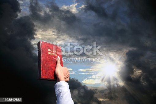 Christianity concept of close up woman hand holding Holy Bible over cloudy sky with shinning sun.