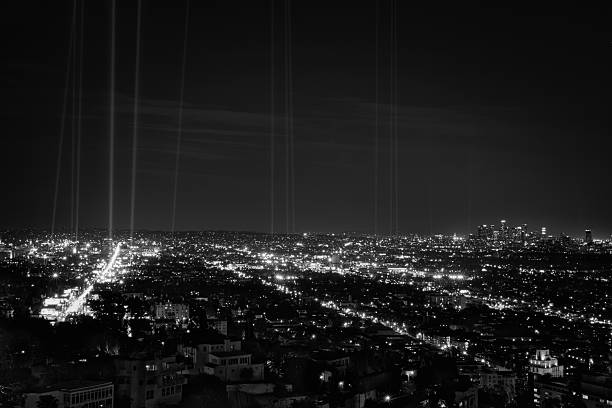 Hollywood and Downtown Los Angeles at night with spot lights Hollywood, west hollywood, and downtown los angeles at night in black and white.  Spot lights are aimed into sky and placed along the route of the 30th anniverary of the LA marathon sunset strip stock pictures, royalty-free photos & images