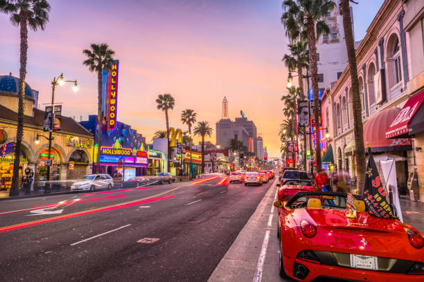 Hollywood Boulevard California Los Angeles: Traffic on Hollywood Boulevard at dusk. The theater district is a famous tourist attraction. hollywood california stock pictures, royalty-free photos & images