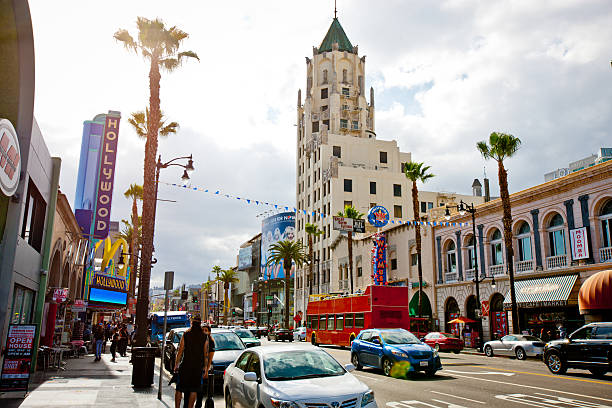 Hollywood Boulevard, Los Angeles, California, USA Los Angeles, USA  - May 7, 2013: Hollywood Boulevard, Los Angeles, California, USA. Cars and people on the street. Sightseeing tour bus moving on boulevard, famous shops and museums. hollywood boulevard stock pictures, royalty-free photos & images