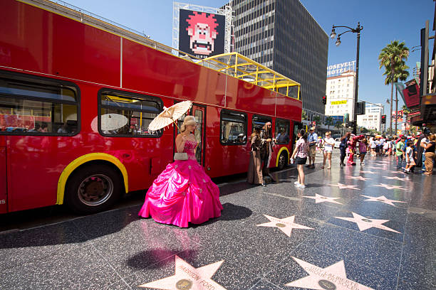 Hollywood Boulevard Hollywood, California, USA - August 11, 2012: Street performer and tourists on the star lined Hollywood Walk of Fame on Hollywood Blvd in Los Angeles, CA on August. 11, 2012. 2400 stars pay tribute artists who have made contributions in entertainment. hollywood boulevard stock pictures, royalty-free photos & images
