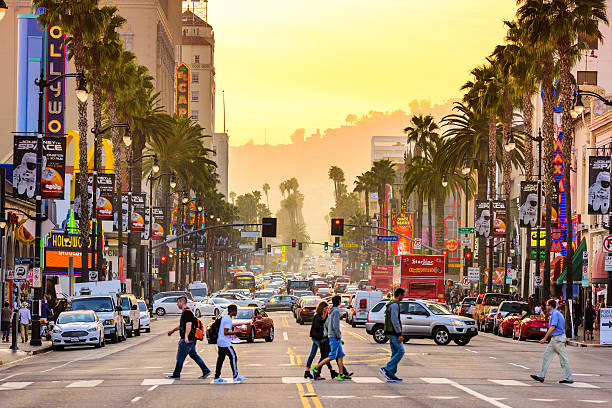 Hollywood Boulevard Los Angeles, USA - March 1, 2016: Pedestrians cross traffic on Hollywood Boulevard at dusk. The road serves as a theater district and major tourist attraction. hollywood boulevard stock pictures, royalty-free photos & images