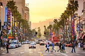 Los Angeles, CA, USA - March 1, 2016: Pedestrians cross traffic on Hollywood Boulevard at dusk. The road serves as a theater district and major tourist attraction.