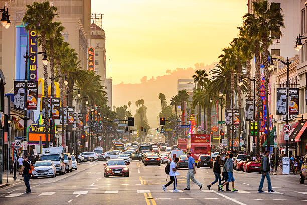 Hollywood California Streets Los Angeles, CA, USA - March 1, 2016: Pedestrians cross traffic on Hollywood Boulevard at dusk. The road serves as a theater district and major tourist attraction. hollywood boulevard stock pictures, royalty-free photos & images