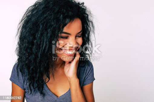 910856488 istock photo Hollywood smile. Cheerful African American girl with bushy messy dark hair is laughing with her eyes closed, touching her neck with the left hand. 1180642742