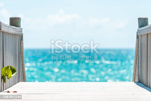 Hollywood, USA Beach boardwalk in Florida Miami with wooden steps stairs and nobody with bokeh blurry blurred background of blue ocean water during day