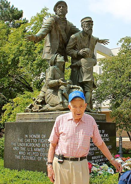 Holocaust Survivor standing at Holocaust Monument stock photo