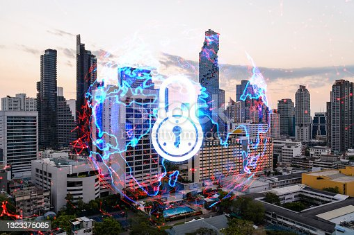 istock Hologram of Padlock on sunset panoramic cityscape of Bangkok, Asia. The concept of cyber security intelligence. Multi exposure. 1323375065