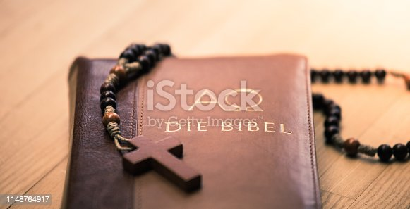 istock Holy bible and rosary: Christian bible and rosary on a wooden desk 1148764917