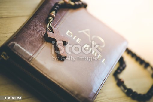 istock Holy bible and rosary: Christian bible and rosary on a wooden desk 1148765268