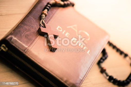 istock Holy bible and rosary: Christian bible and rosary on a wooden desk 1148765270