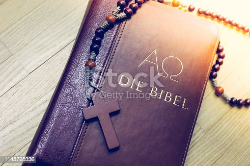 istock Holy bible and rosary: Christian bible and rosary on a wooden desk 1148765336