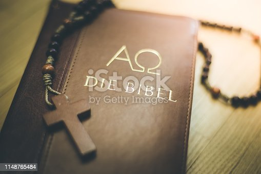 istock Holy bible and rosary: Christian bible and rosary on a wooden desk 1148765484