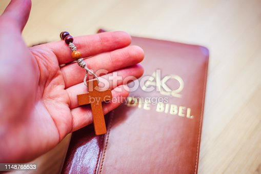 istock Holy bible and rosary: Christian bible and rosary on a wooden desk 1148765533