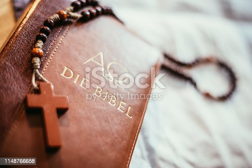 istock Holy bible and rosary: Christian bible and rosary on a wooden desk 1148766658