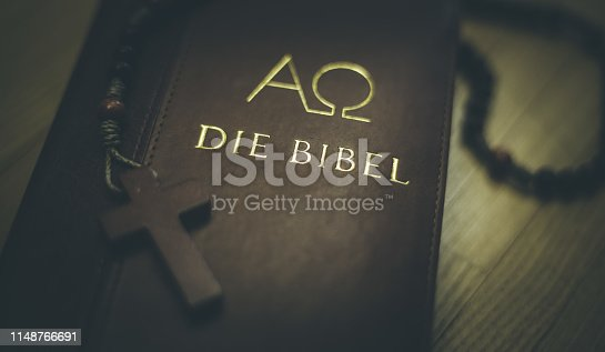 istock Holy bible and rosary: Christian bible and rosary on a wooden desk 1148766691
