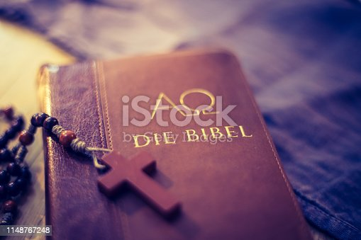 istock Holy bible and rosary: Christian bible and rosary on a wooden desk 1148767248