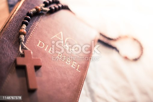 istock Holy bible and rosary: Christian bible and rosary on a wooden desk 1148767378